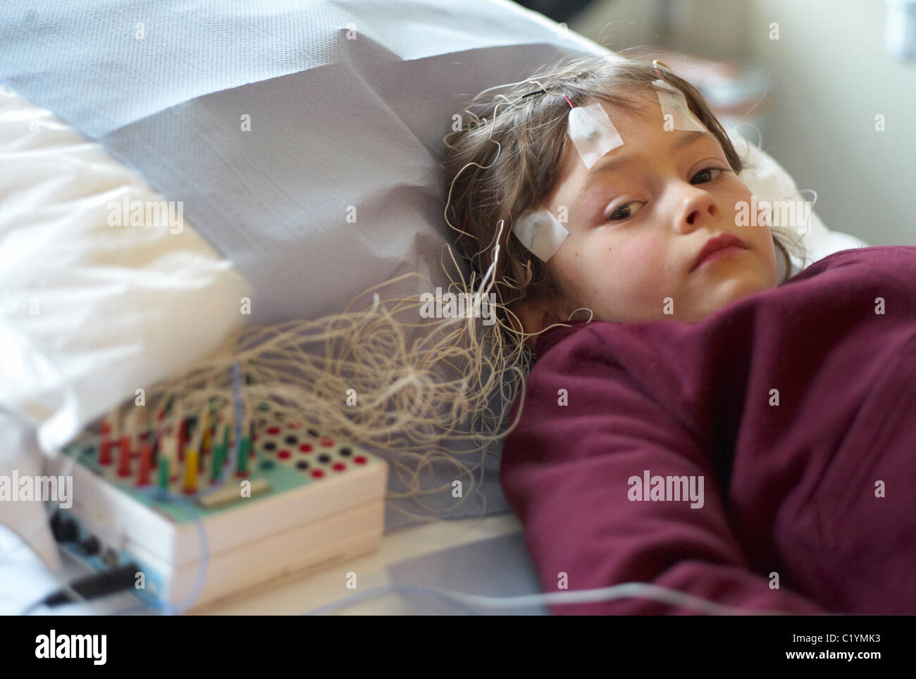 Child in a hospital out patient department undergoing an EEG or brain scan - Stock Image