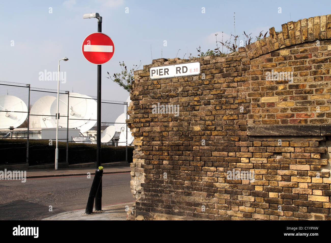 UK. OLD BRICK WALL NEAR SATELLITE DISHES IN THE LONDON DOCKLANDS - Stock Image