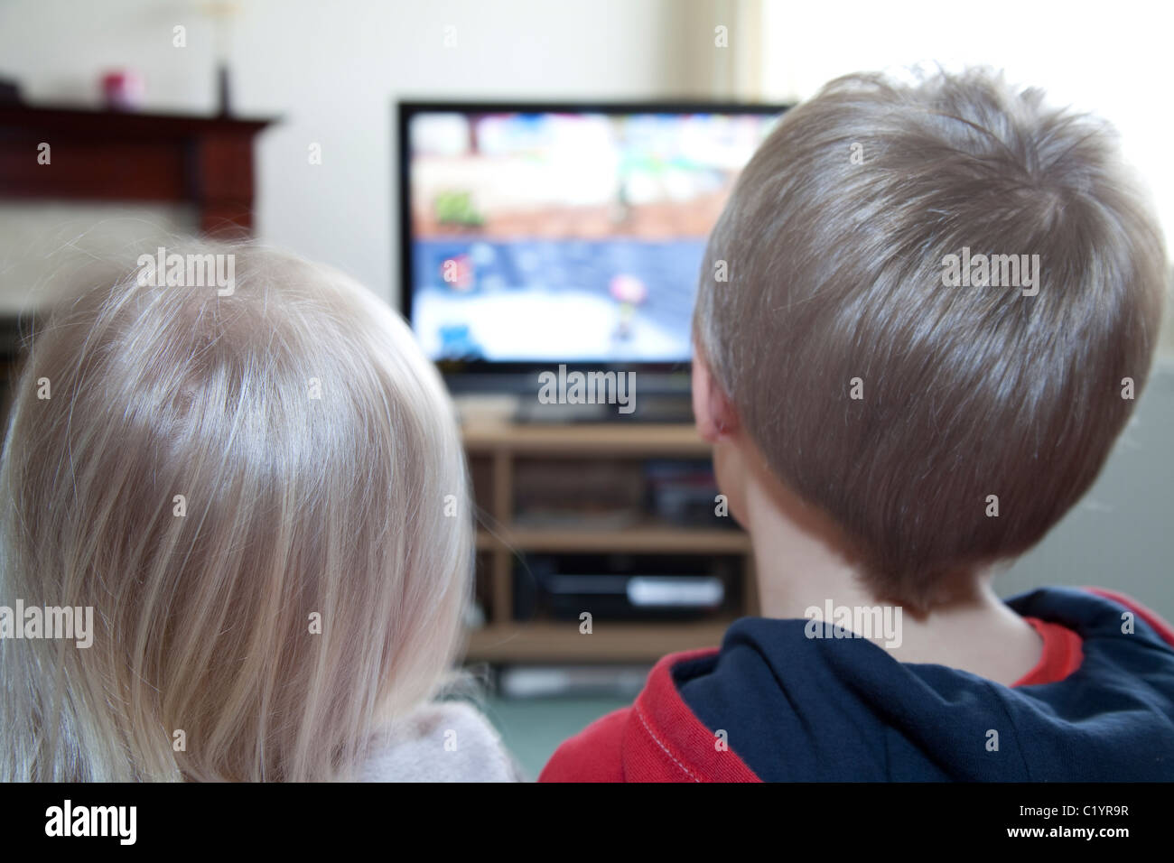 A young brother and sister watch TV together in the family home England UK - Stock Image