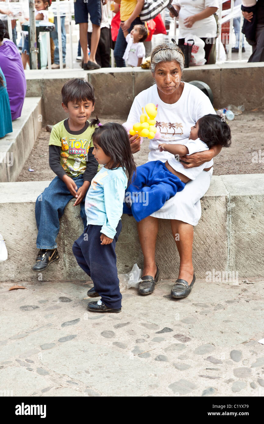 abstracted handsome Mexican grandmother minding three lively grandchildren at festival in Benito Juarez Llano park - Stock Image