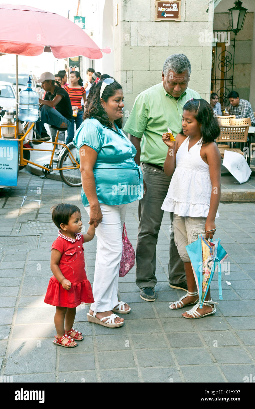 Mexican tween girl reads her fortune in Oaxaca Zocalo while family members mother father & cute little sister - Stock Image
