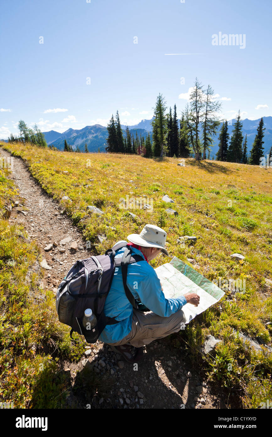 A hiker on the Pacific Crest Trail checking his map. Washington Cascades, USA. Stock Photo
