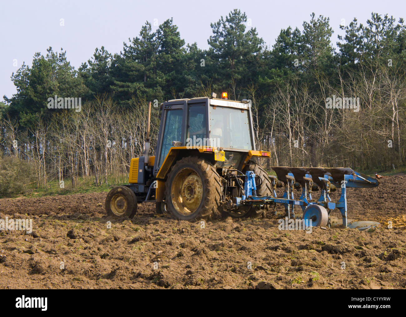 Man in a small tractor ploughing a field with a plough. - Stock Image