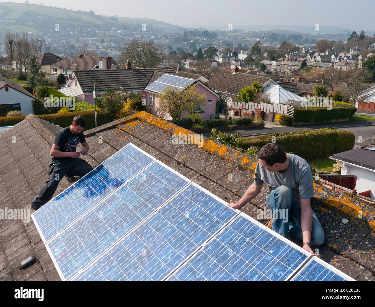 Photovoltaic solar panels being fitted to a roof in Totnes Devon UK - Stock Image