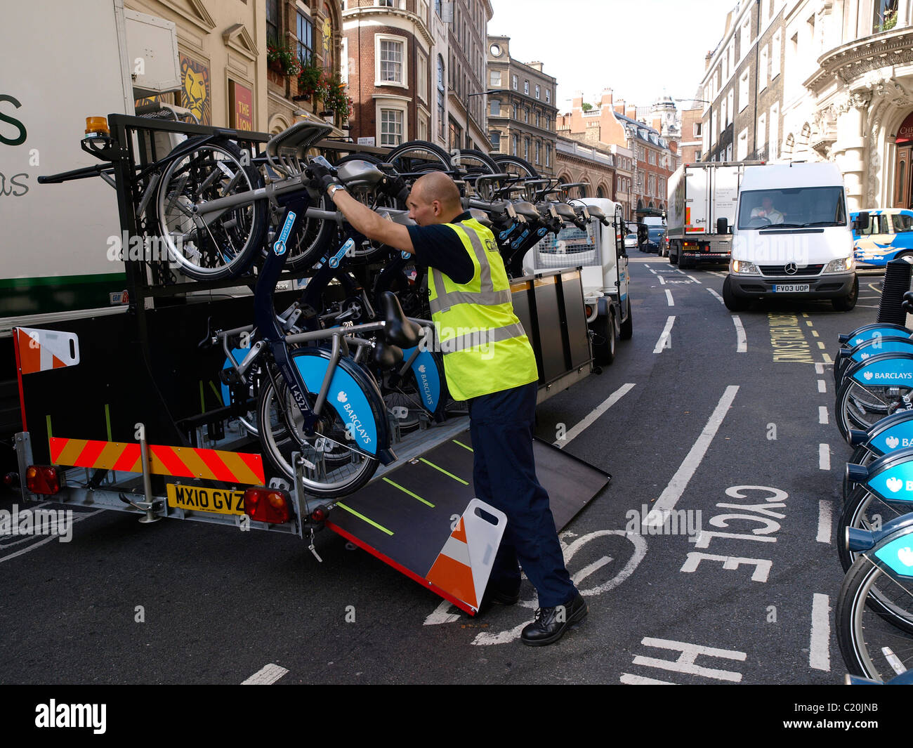Barclays TFL bicycle scheme maintenance worker loading a bicycle onto a trailer to be taken for repair. - Stock Image