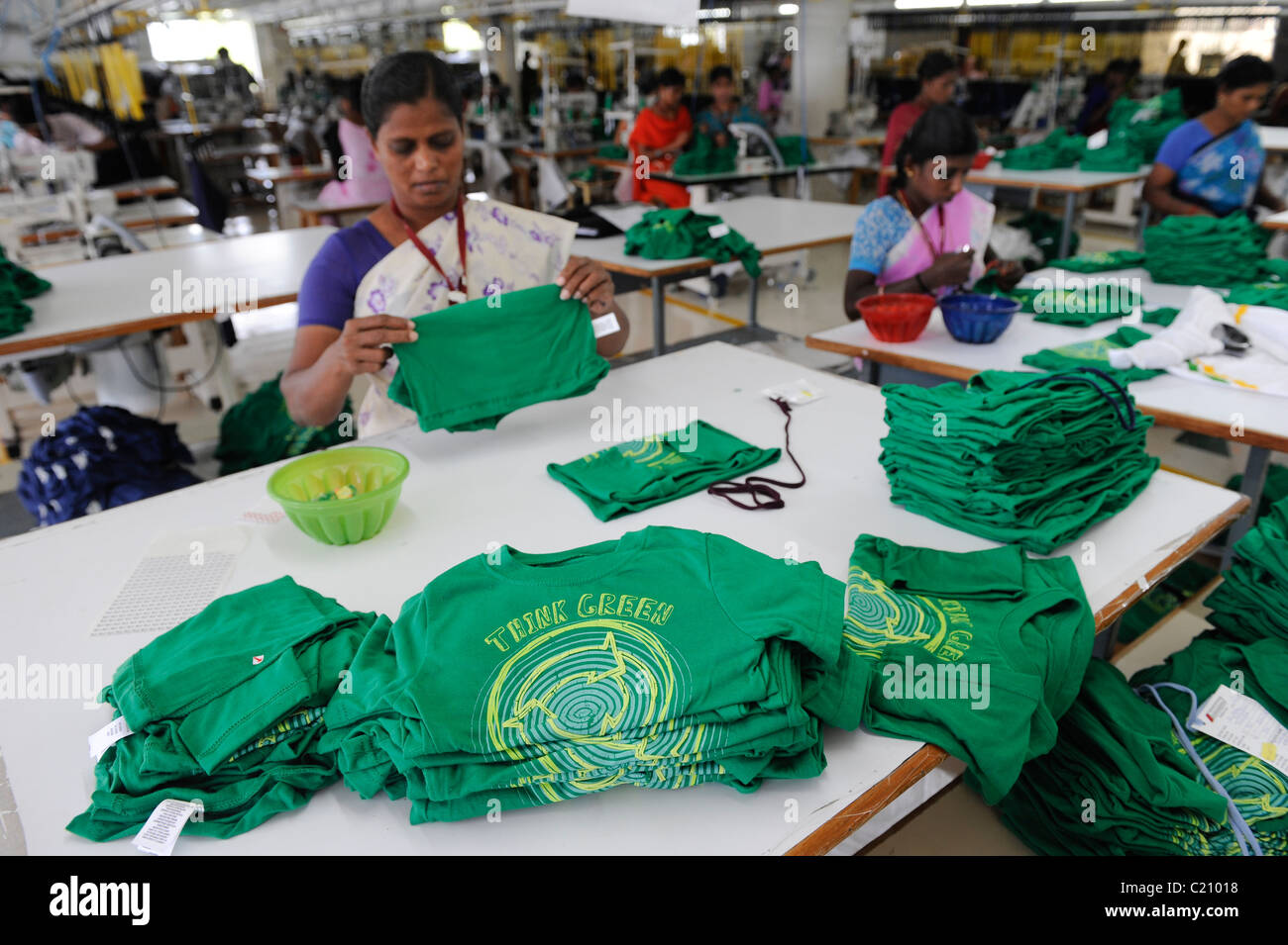India, Tamil Nadu, Tirupur , women work in fair trade textile factory, production of green T-shirt with the printed - Stock Image