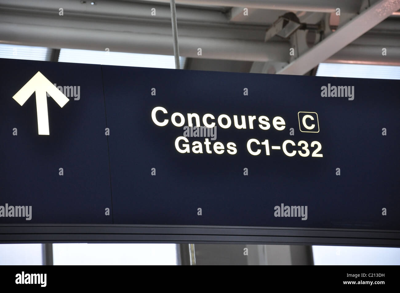 a dark blue airport sign reading Concourse C and Gates C1 to C32 in white with a directional arrow - Stock Image