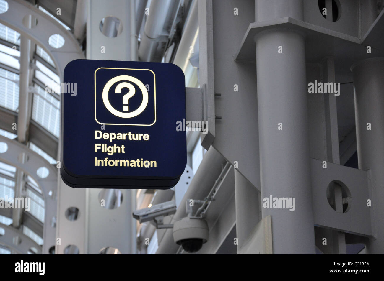 A dark blue sign reading Departure Flight Information with a question mark symbol against a gray industrial background - Stock Image