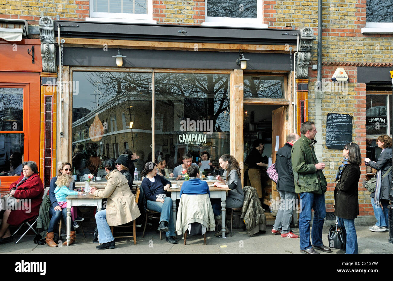 People eating outside Campania Gastronomia restaurant in Columbia Road Flower Market Tower Hamlets London England - Stock Image