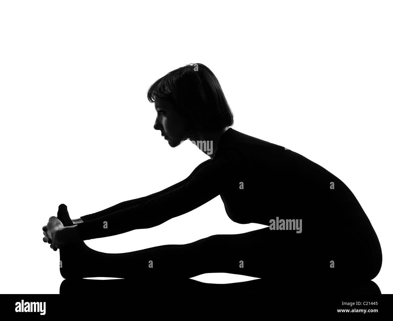 woman paschimottanasana yoga pose posture position in silouhette on studio white background full length - Stock Image