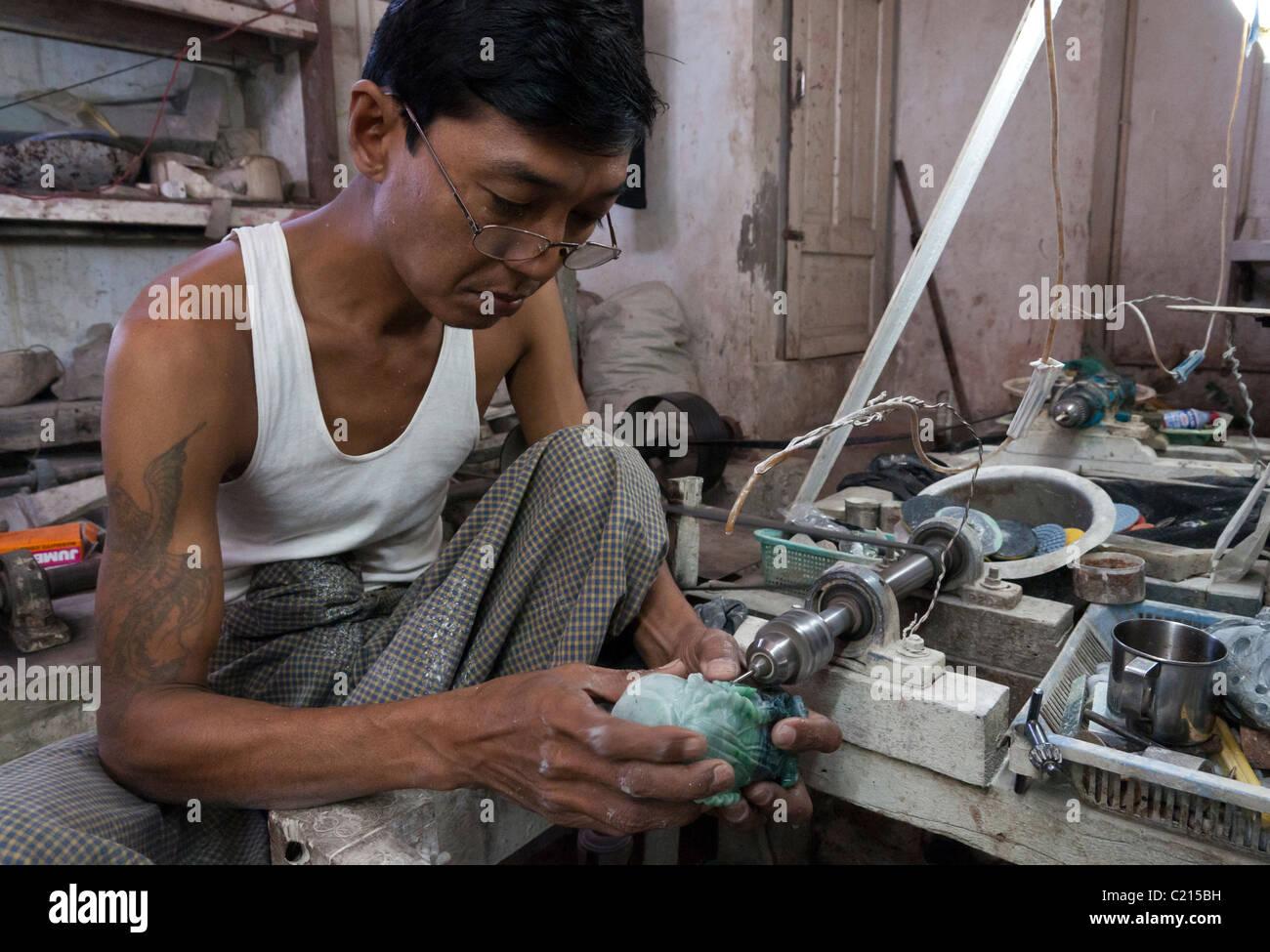 man carving a jade stone in workshop. Yangon. Myanmar - Stock Image