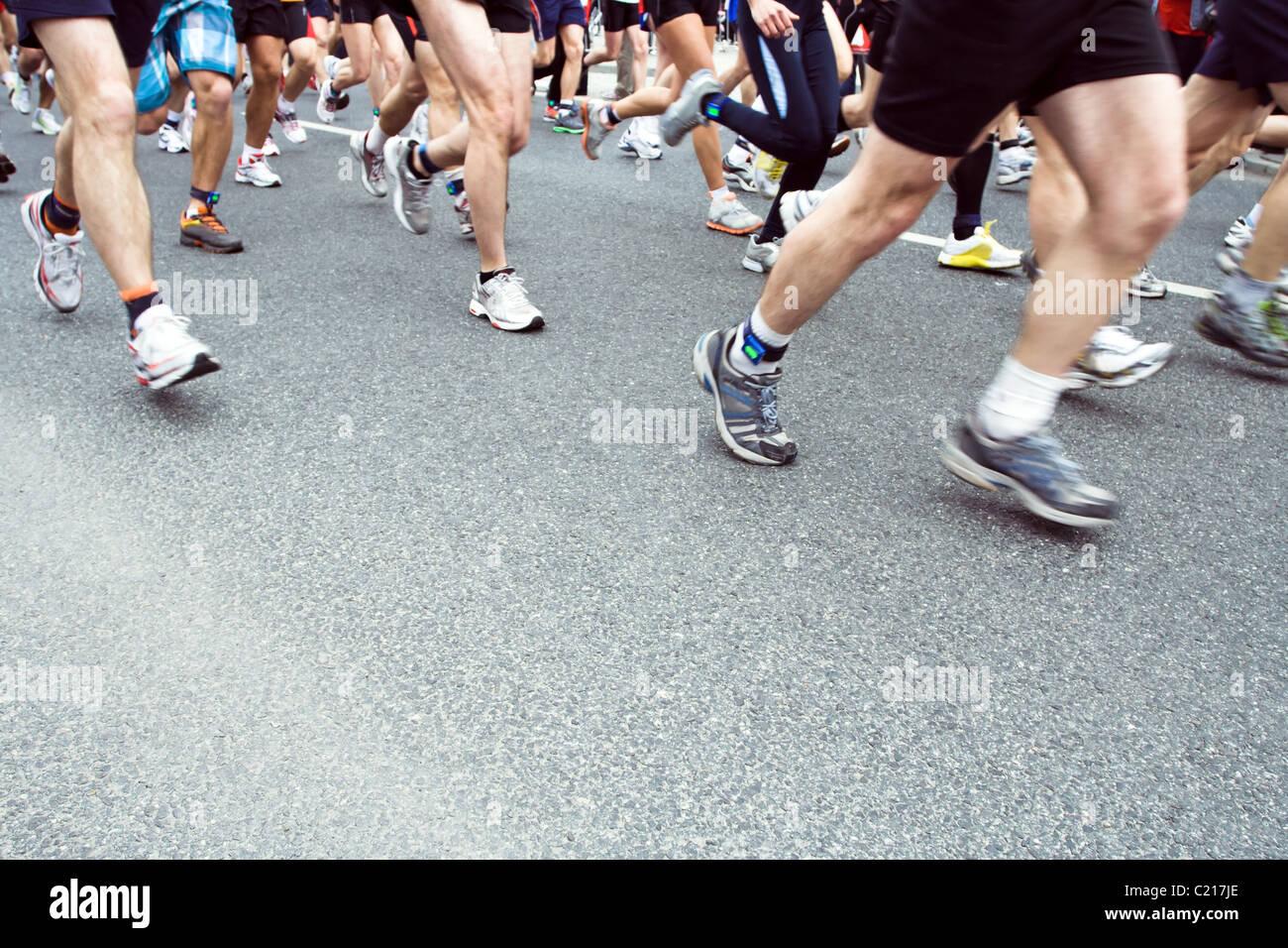 Runners running in city marathon, motion blur on legs - Stock Image