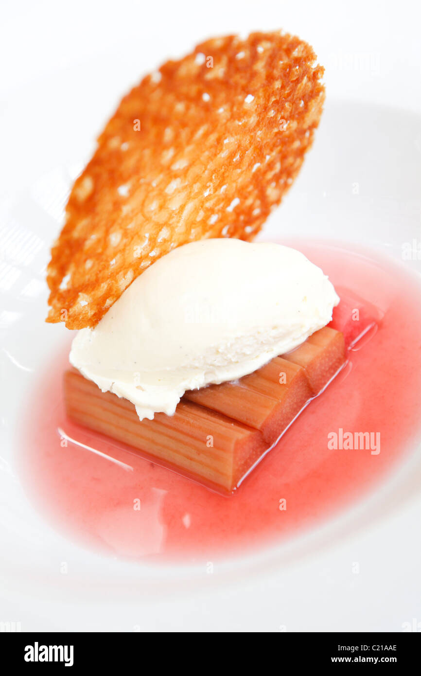 Dessert of spiced rhubarb with cream and a brandy snap biscuit. - Stock Image