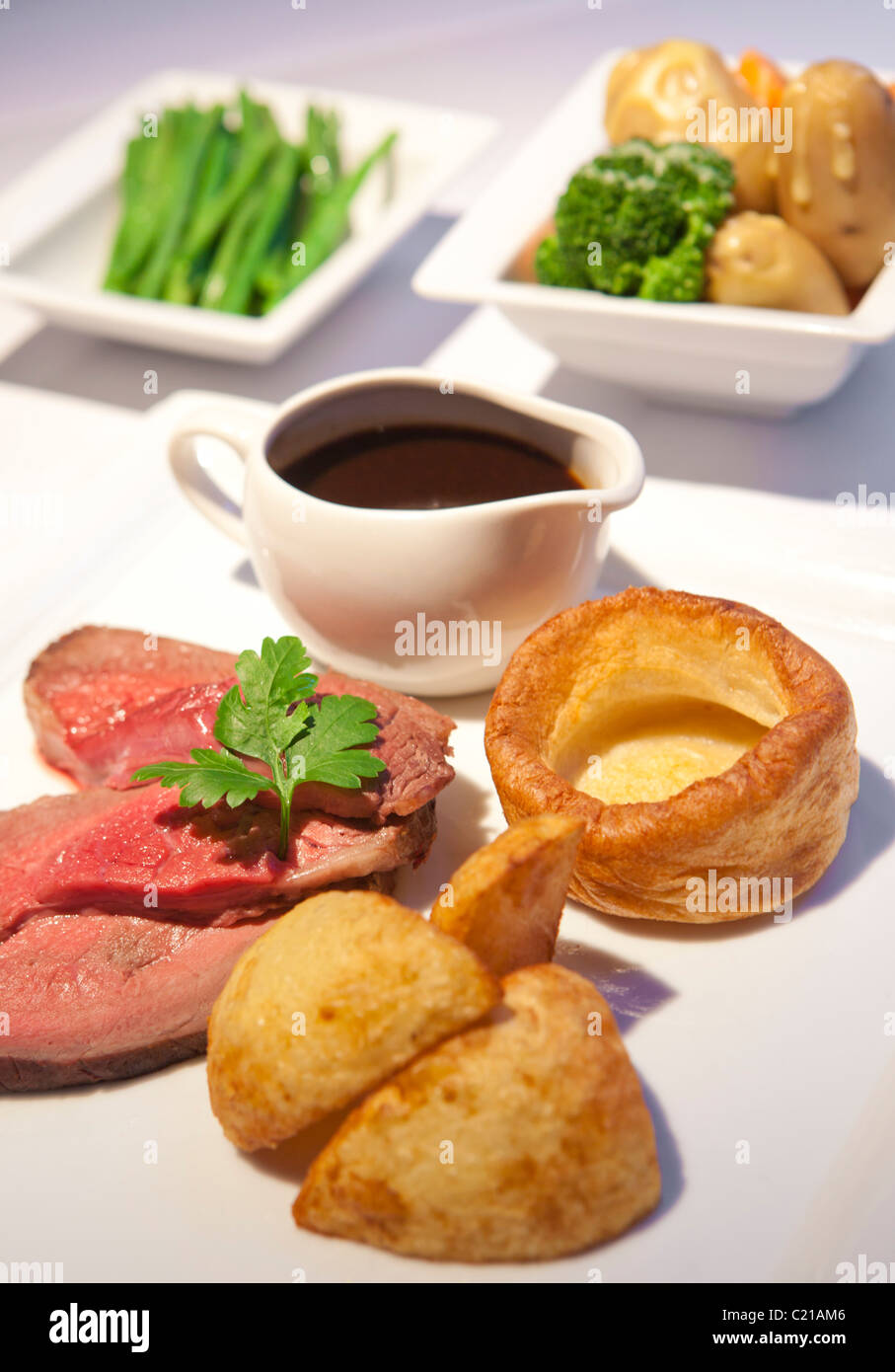 Traditional rare roast beef sunday dinner with vegtables and gravy. Stock Photo