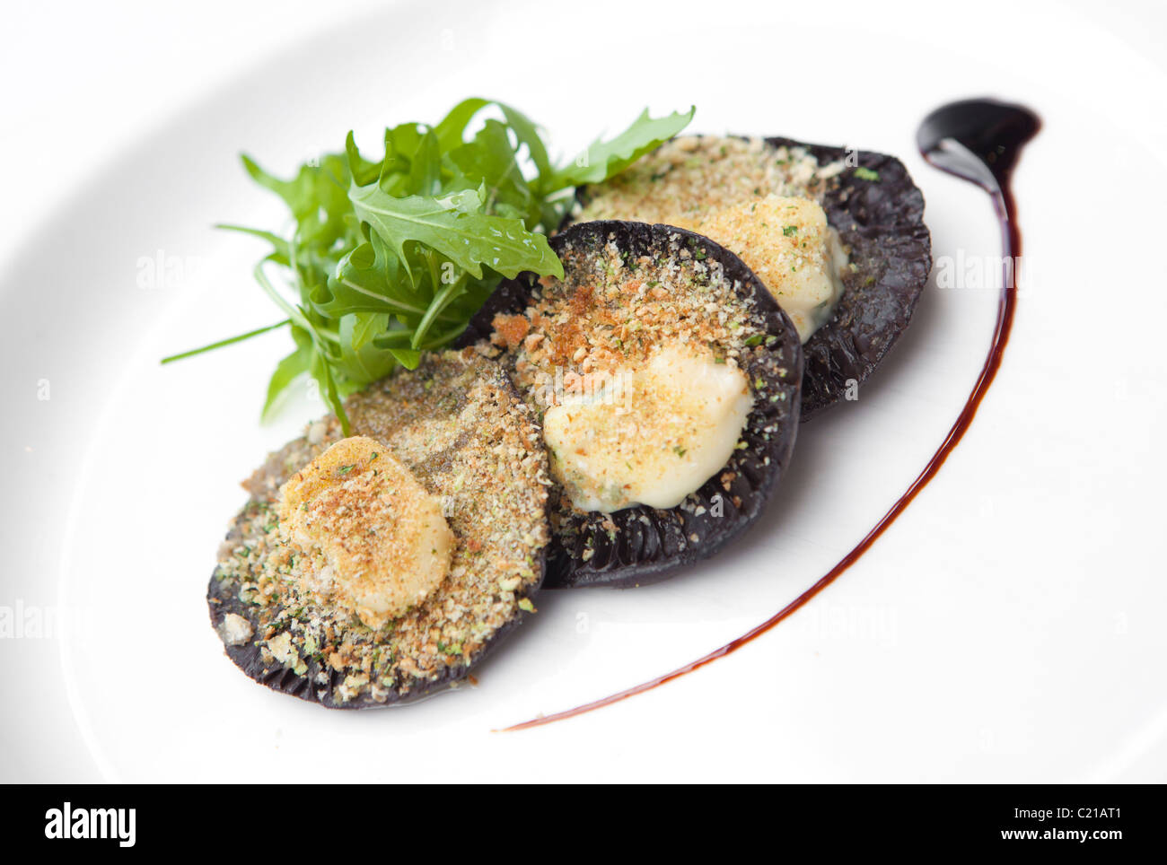 Starter of large flat mushrooms stuffed with breadcrumbs and cheese served with rocket salad and balsamic dressing. - Stock Image