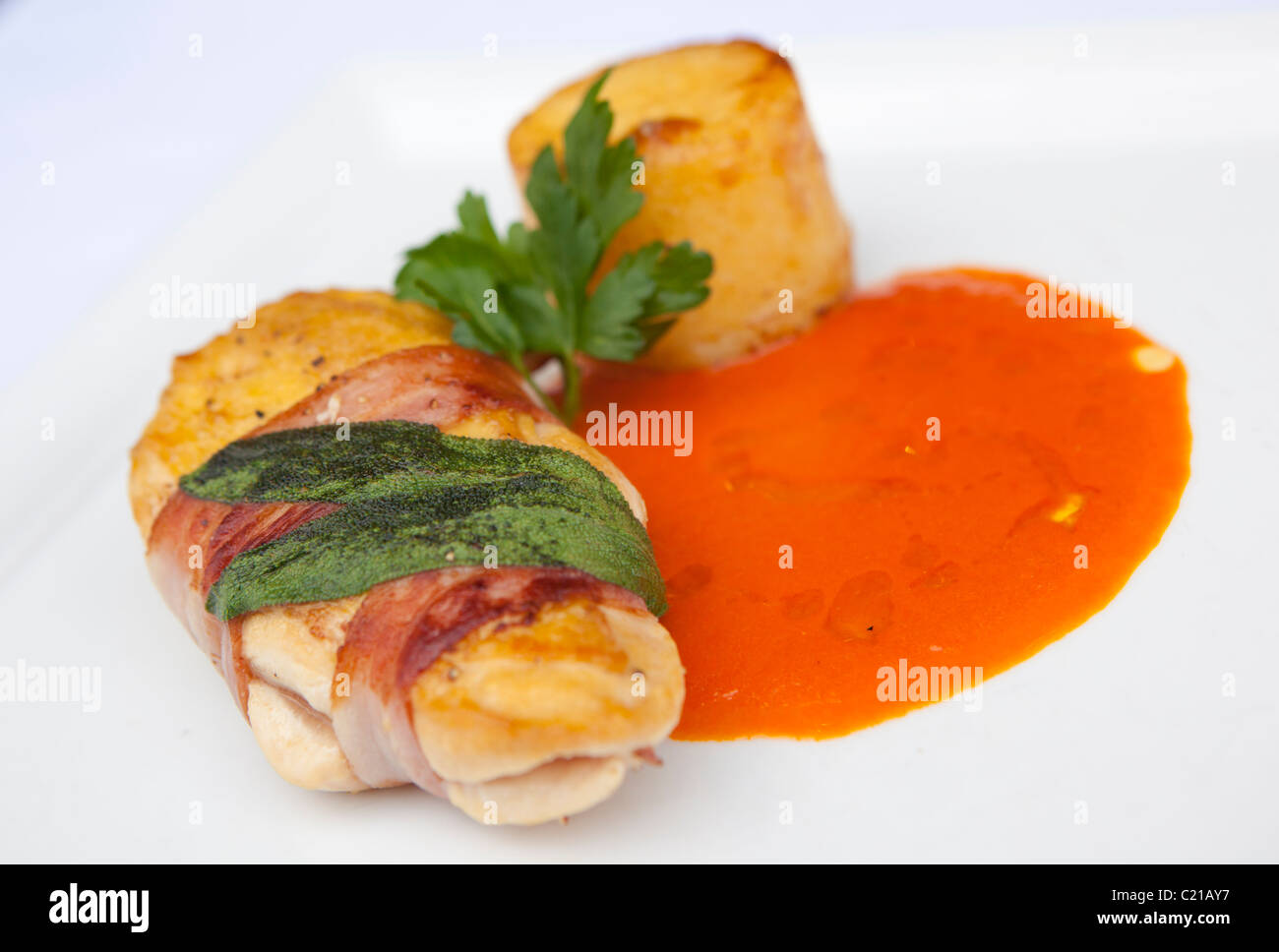 Main meal of chicken wrapped in parma ham with a tomato and mascarpone jus. - Stock Image