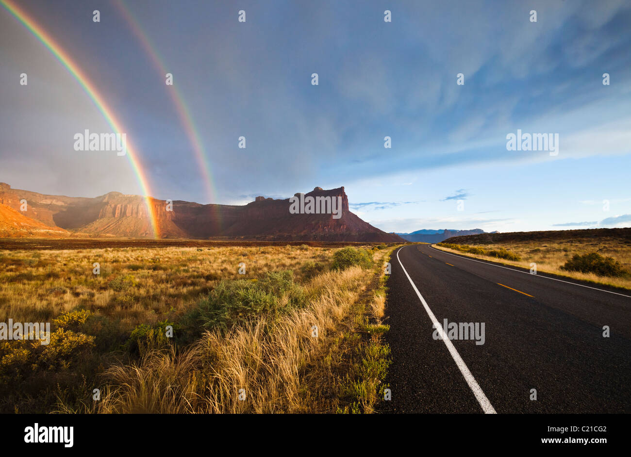 Highway 211, mesas, and a rainbow in the desert of Southeast Utah, USA. - Stock Image