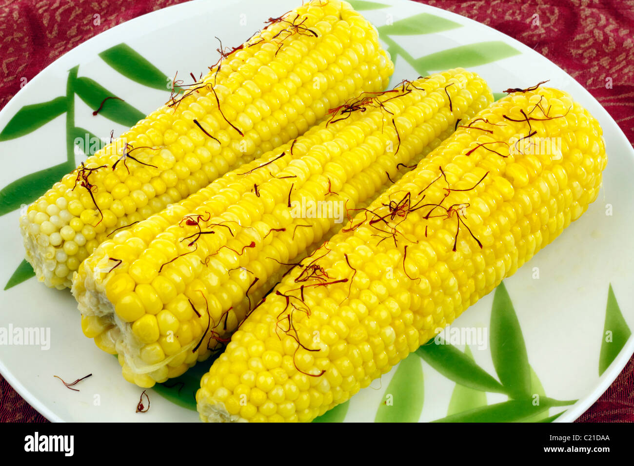Three bright, buttered yellow vegetable ears topped with strands of red orange crocus stigmas. Interesting way to - Stock Image