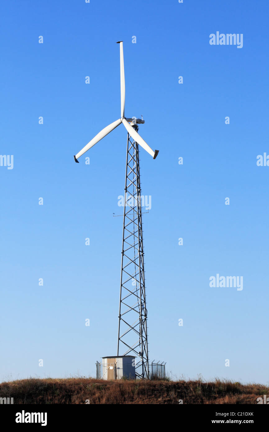 vertical image of tall electric windmill or wind turbine with blue sky background - Stock Image
