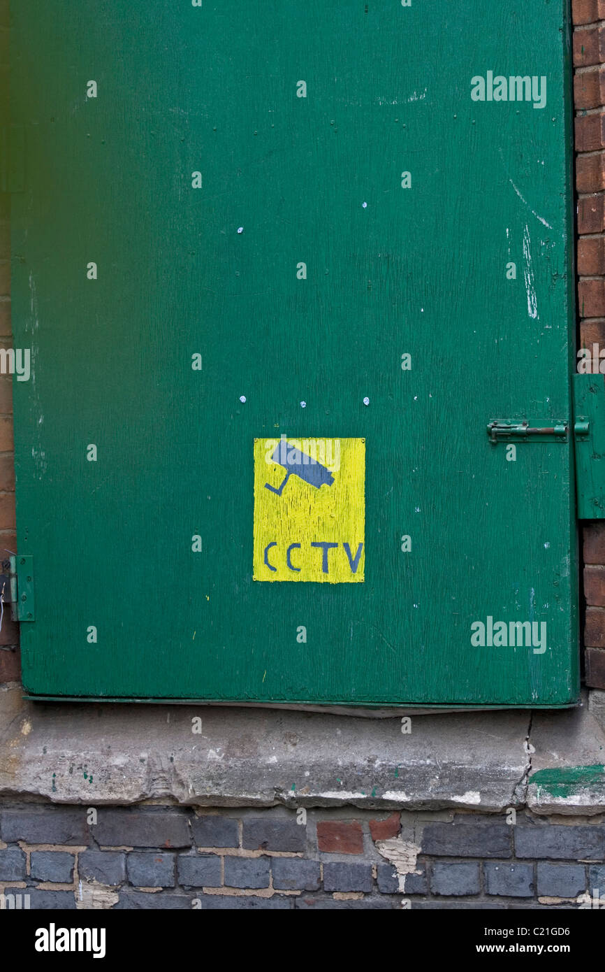 A hand painted CCTV notice on a building - Stock Image