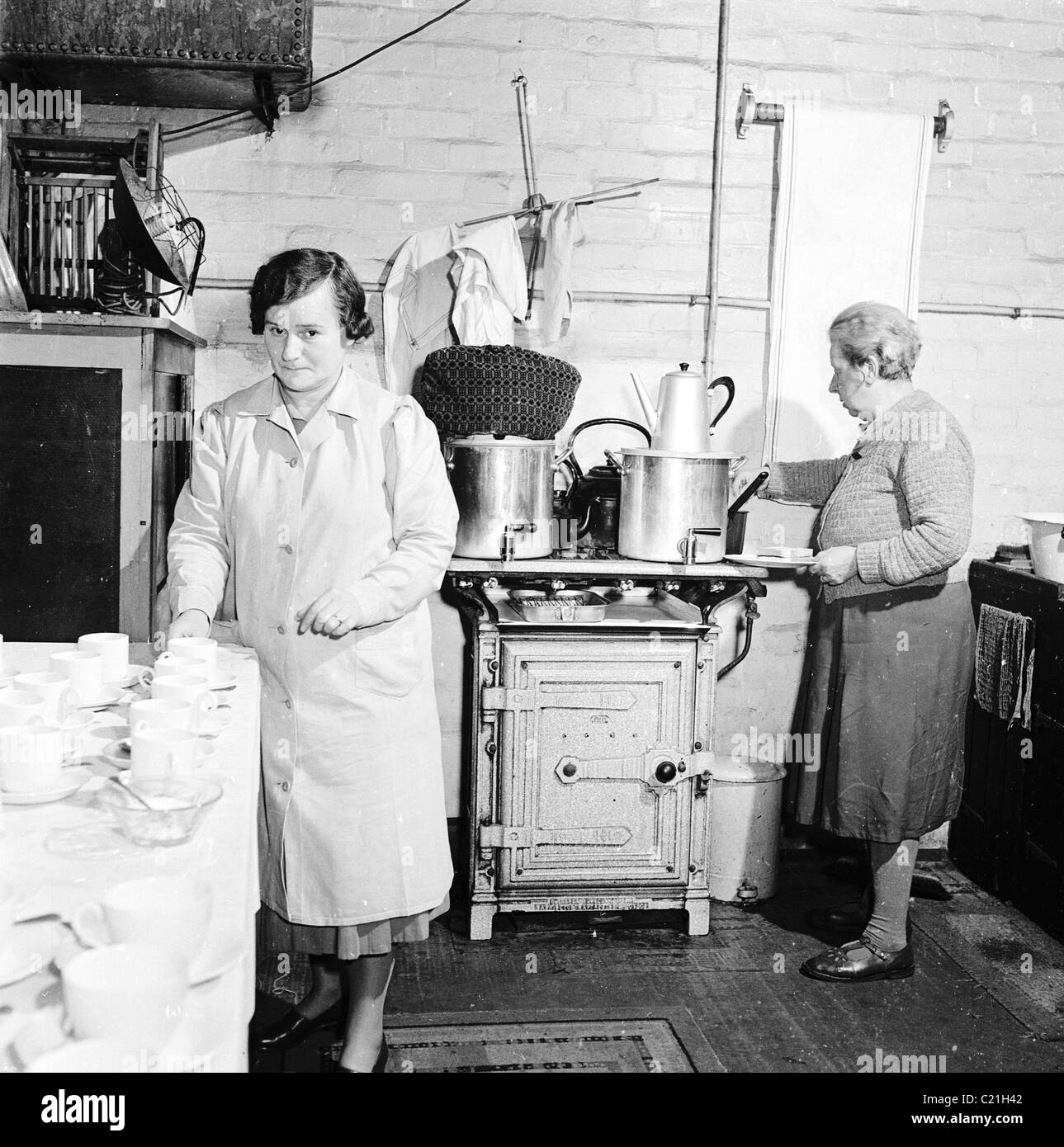 1950s, England. Two women making tea in a factory kitchen, in this ...