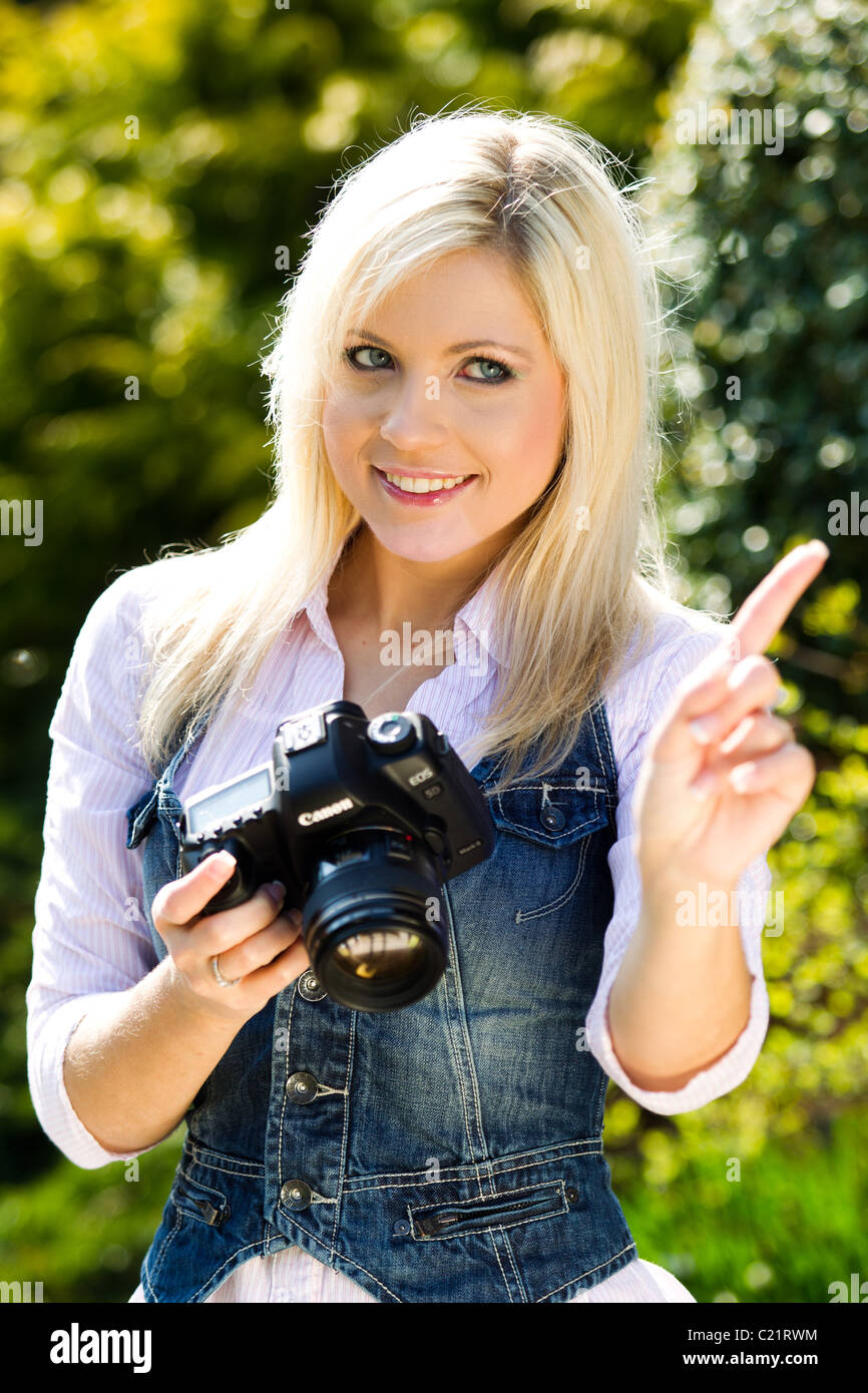 Girl taking picture with camera - Stock Image