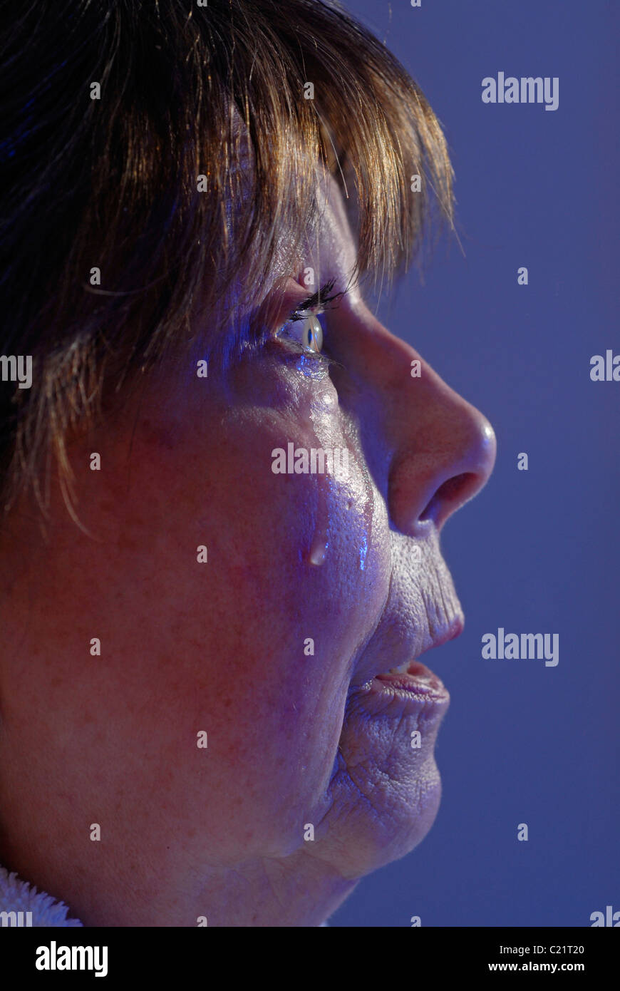 An elderly woman is crying. She is photographed in profile - Stock Image
