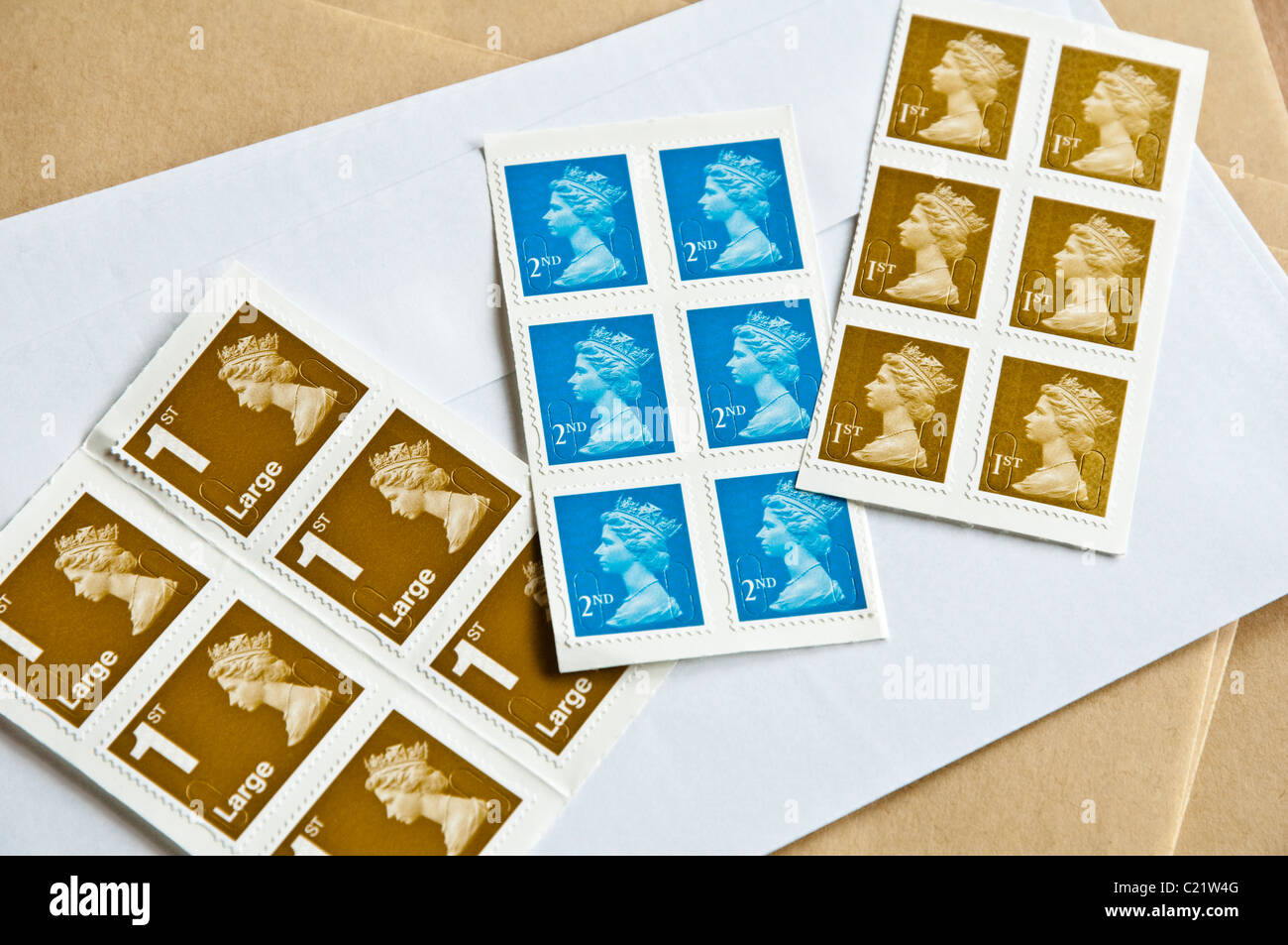 A range of UK stamps and envelopes - including Large 1st Class, 2nd Class and 1st Class postage stamps. - Stock Image