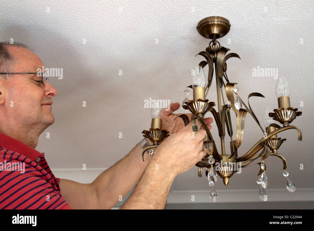 Electrician adds finishing touches to a lightfitting. © StockPix.eu - Stock Image