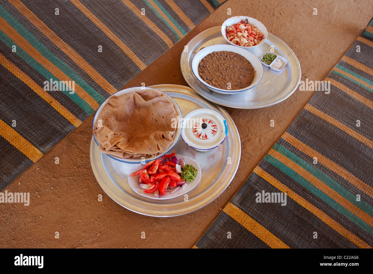 Sudanese meal on a floor. There is bowl of 'ful' - brown stewed beans, served with salad and bread (known - Stock Image
