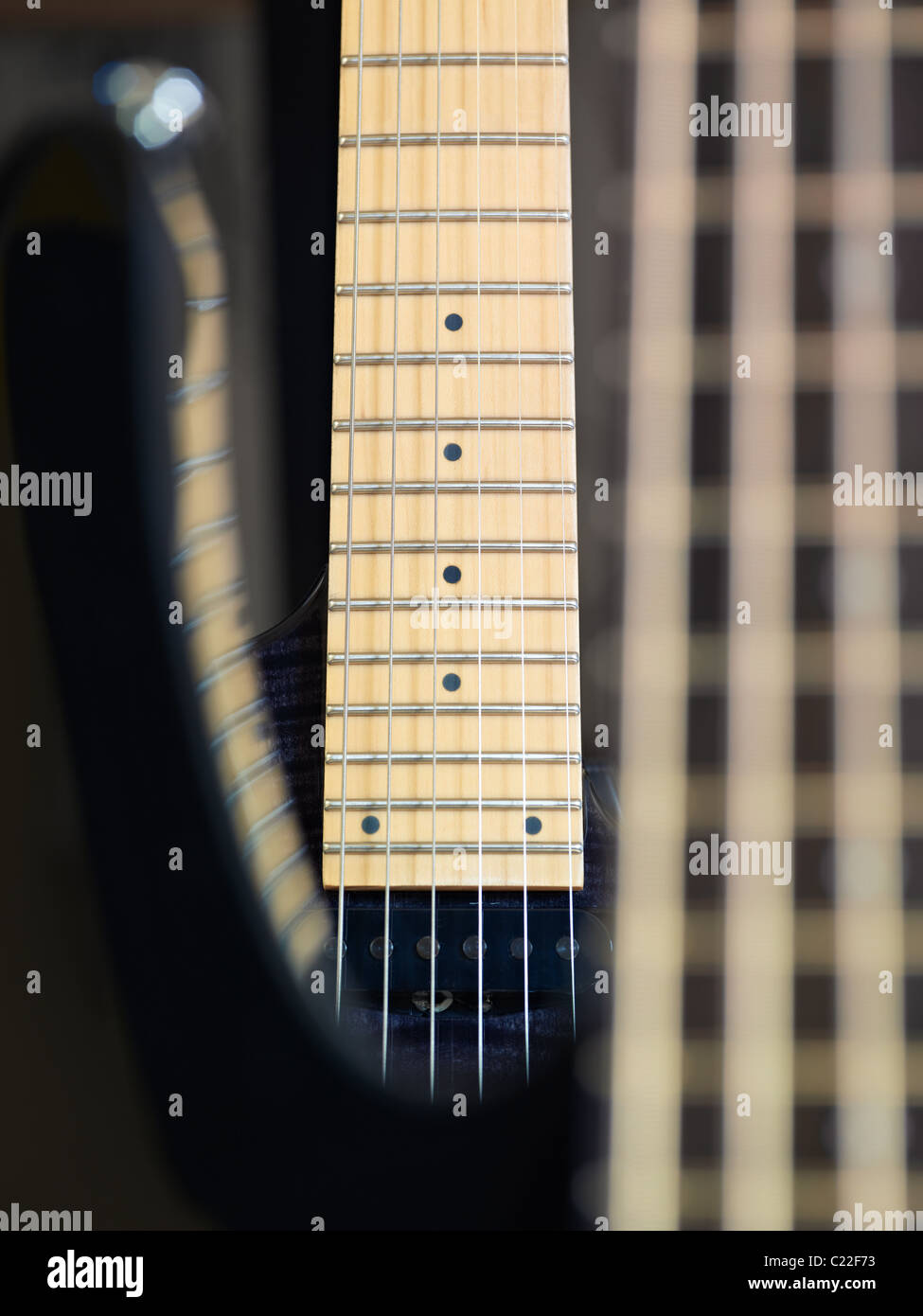 closeup of electric guitar and fretboard. Vertical shape, studio shot, focus on background - Stock Image