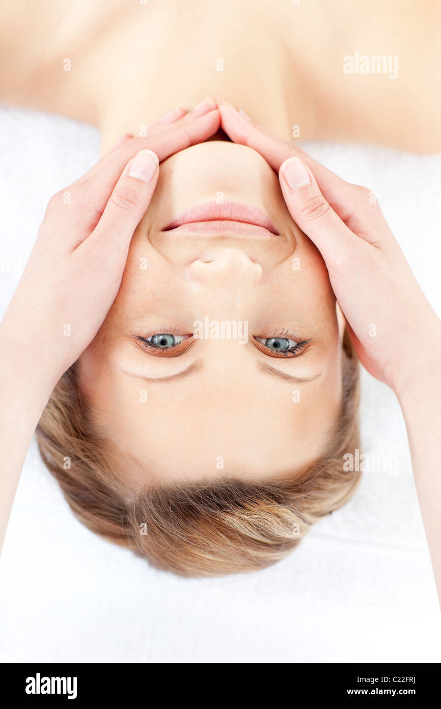 Positive woman receiving a facial massage smiling at the camera Stock Photo
