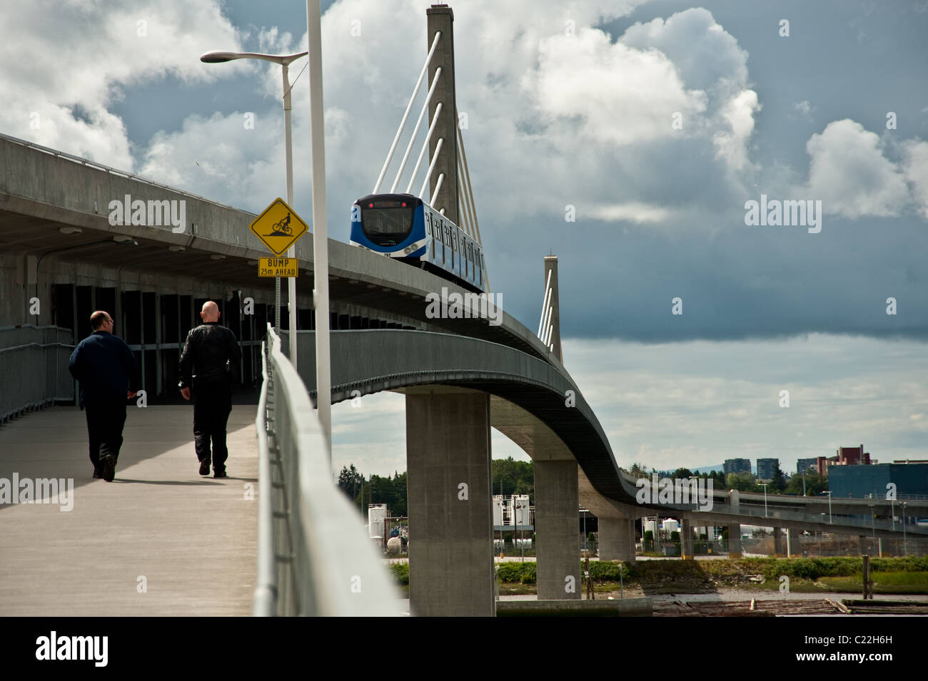 Two people walking by a light rail overpass in a sunny morning in Vancouver, BC, Cananda - Stock Image