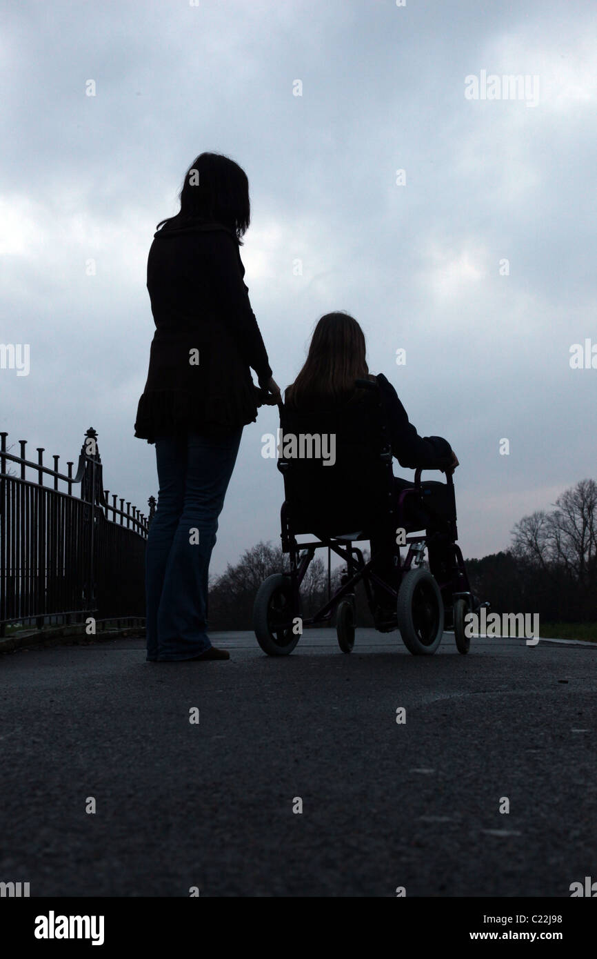 Young girl sitting in a wheelchair with a woman standing by her side - Stock Image