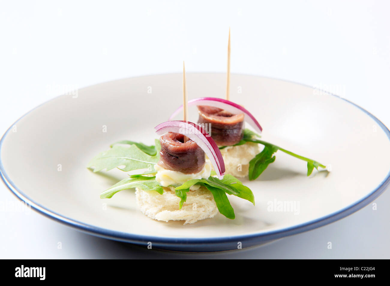 Anchovy canapes garnished with leaves of arugula - Stock Image
