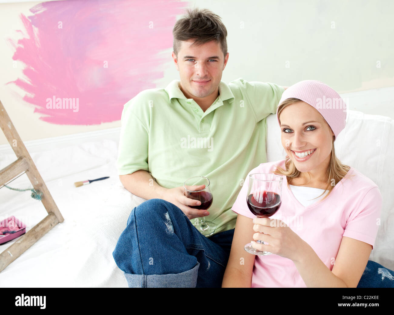 Delighted couple having free time together with a glass of wine smiling at the camera - Stock Image