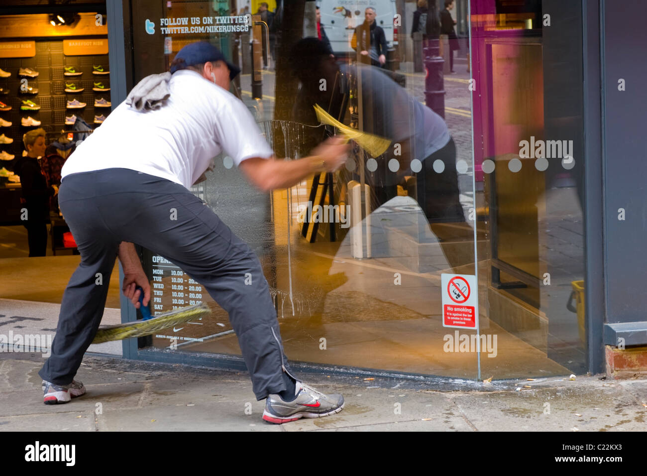 Covent Garden , middle aged man in baseball cap cleans shop or store window with sponge & squeegee motion blur - Stock Image