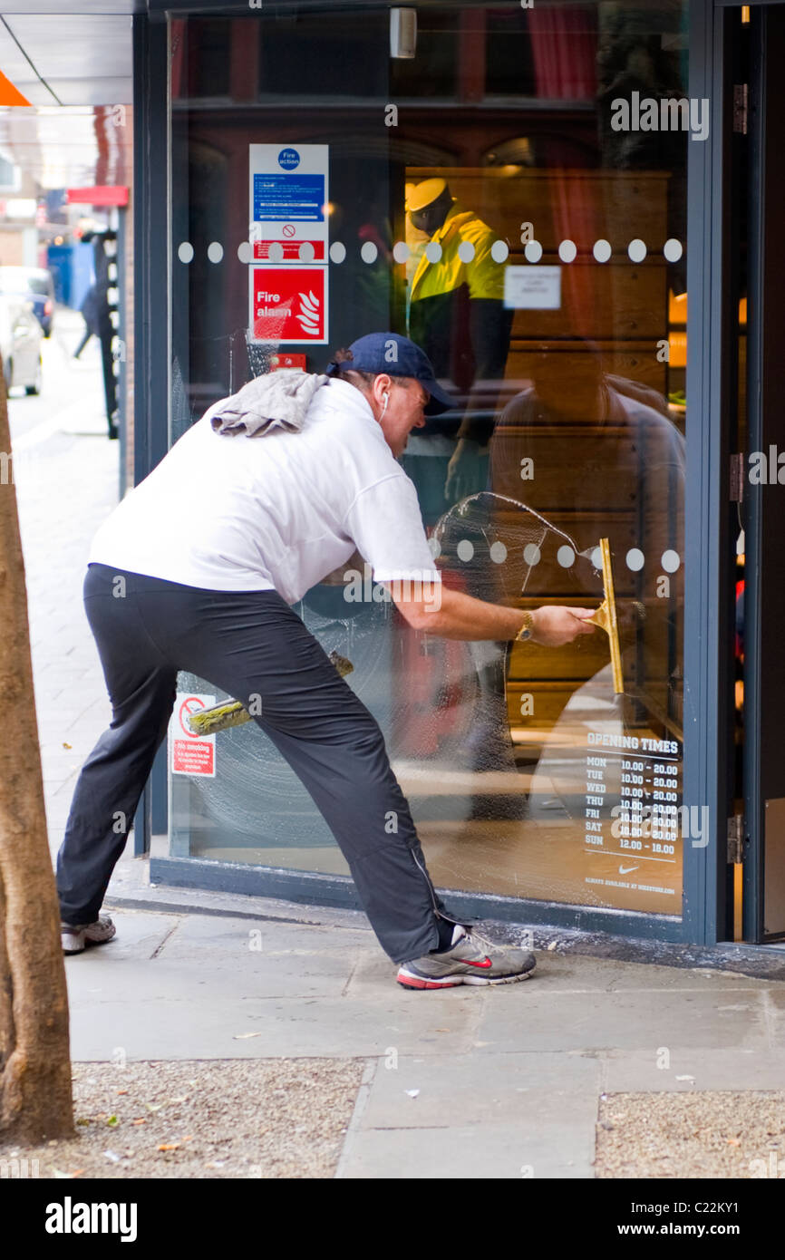 Covent Garden , British workman at work , middle aged window cleaner at work with squeegee & sponge on shop - Stock Image