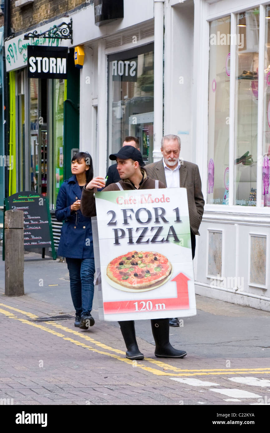 London , Covent Garden , sandwich board man , in baseball cap , Cafe Mode , 2 for 1 pizza offer - Stock Image