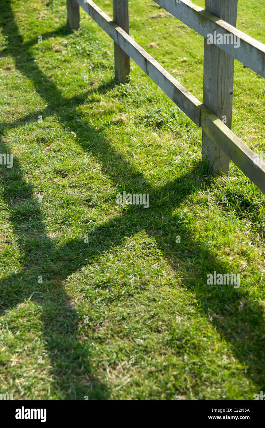 A wooden fence casting a shadow on the grass below, Warwickshire, England, UK - Stock Image