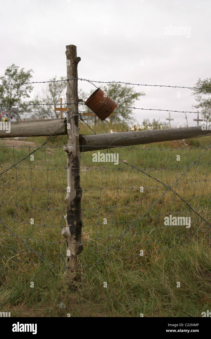 Rusted can hanging on a fence post at the Wounded Knee Memorial in South Dakota. - Stock Image