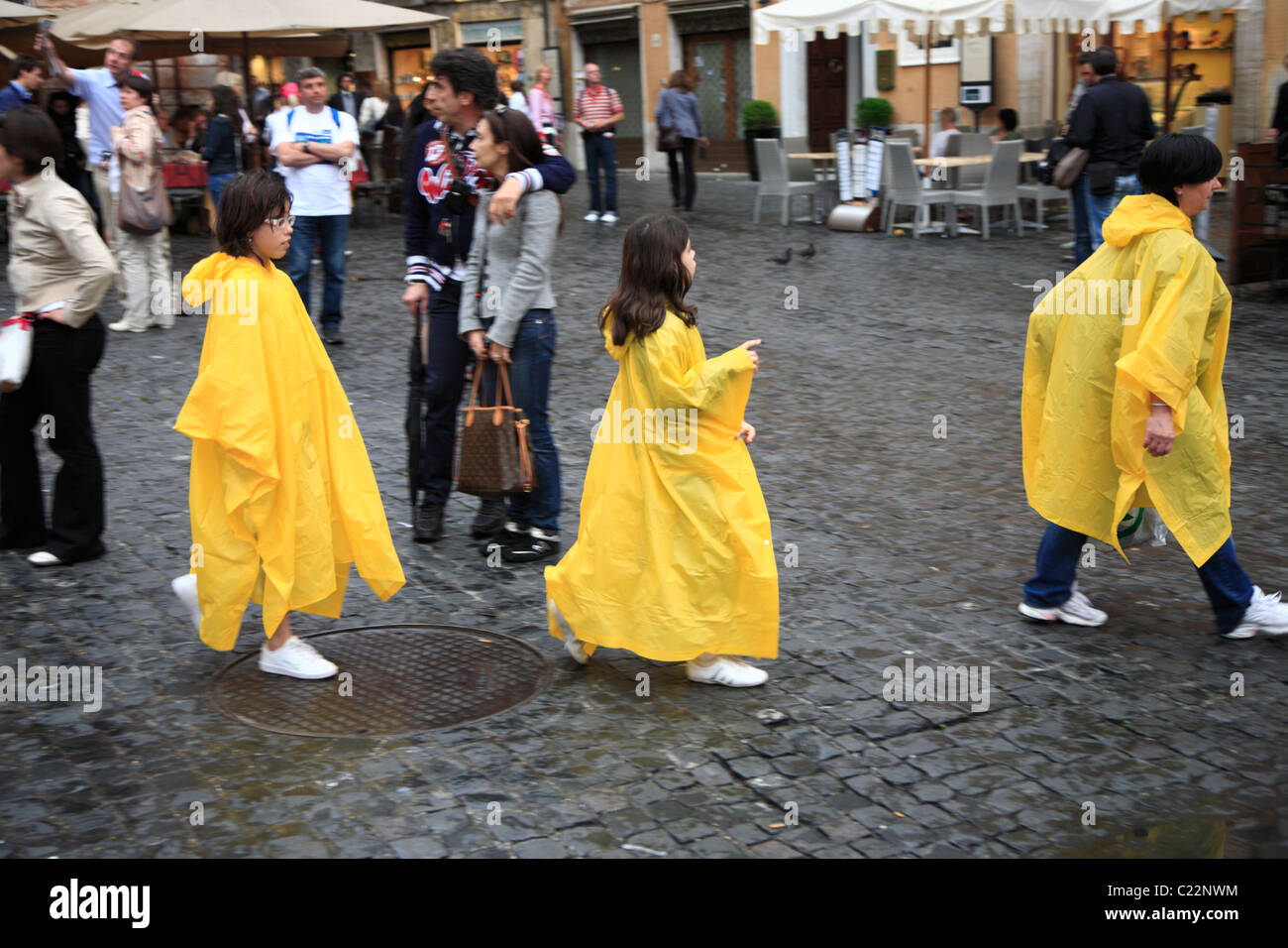 mother and two daughters wearing rainproof bright yellow ponchos - Stock Image