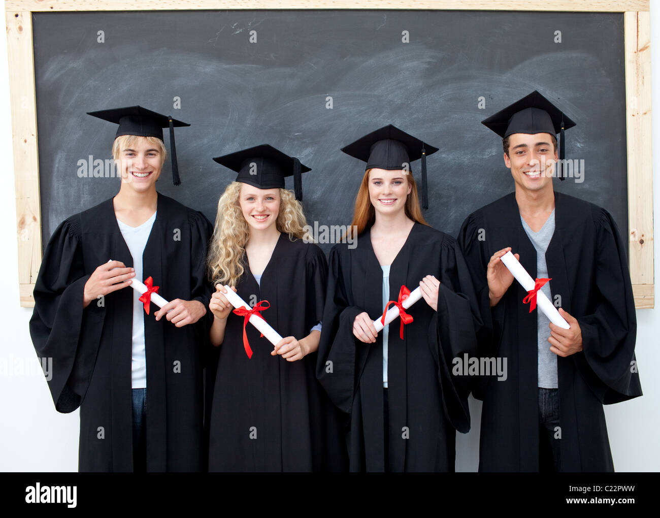 Group of adolescents celebrating after Graduation - Stock Image
