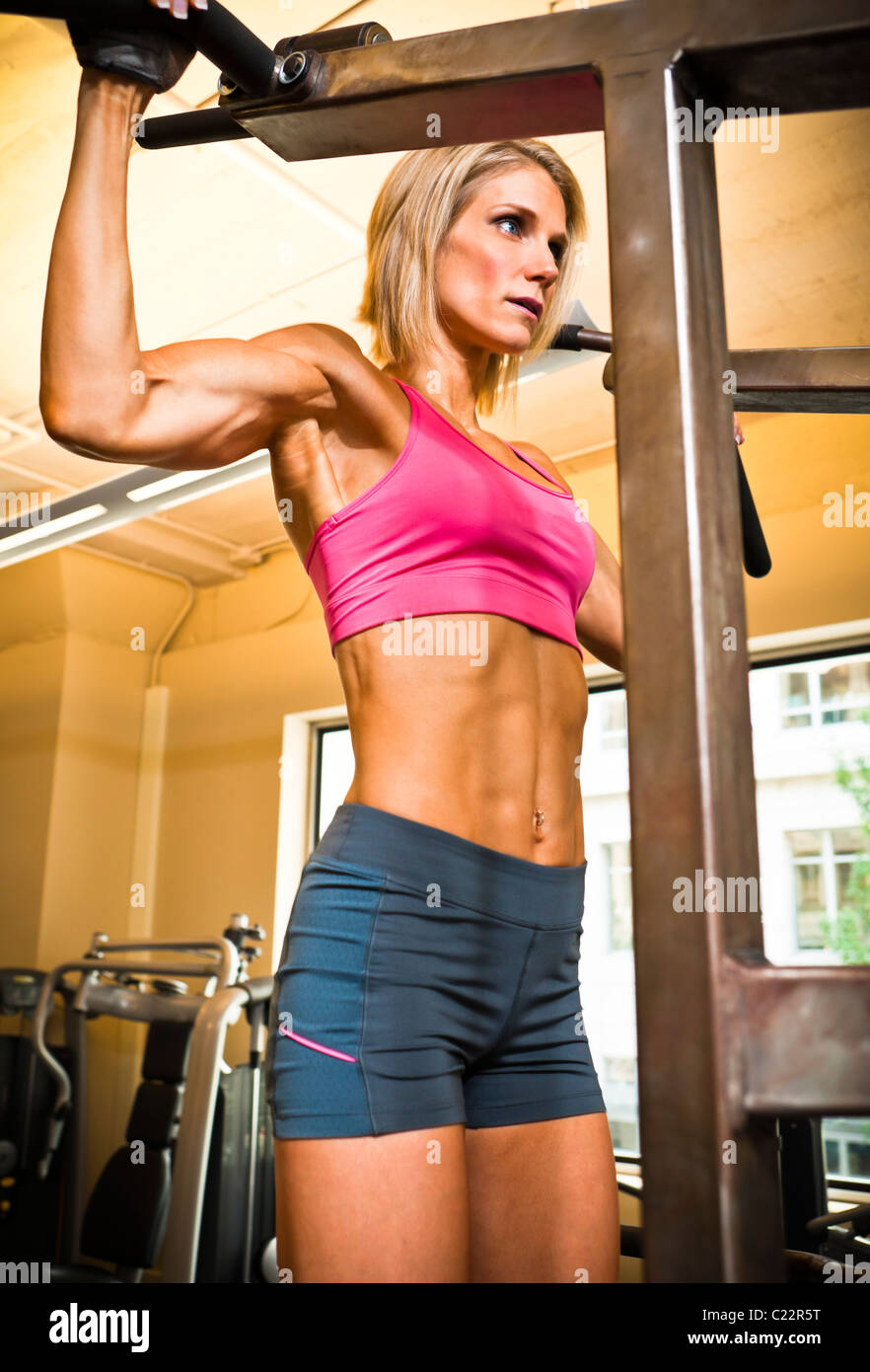 Physically fit woman on a pull-up machine in a health club. - Stock Image