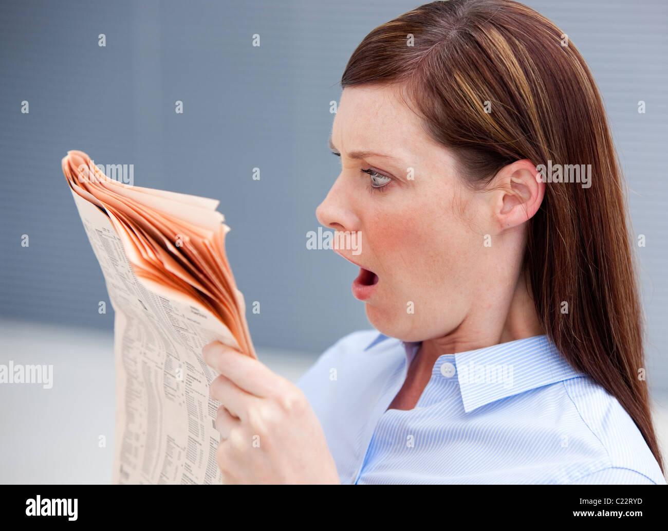 Astonished businesswoman reading newspaper - Stock Image