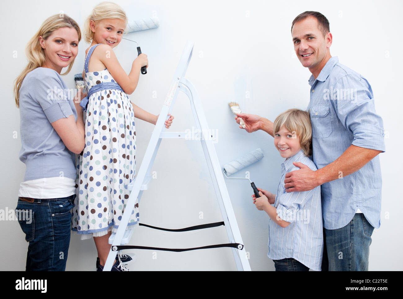 Lively Family Painting A Wall In New House