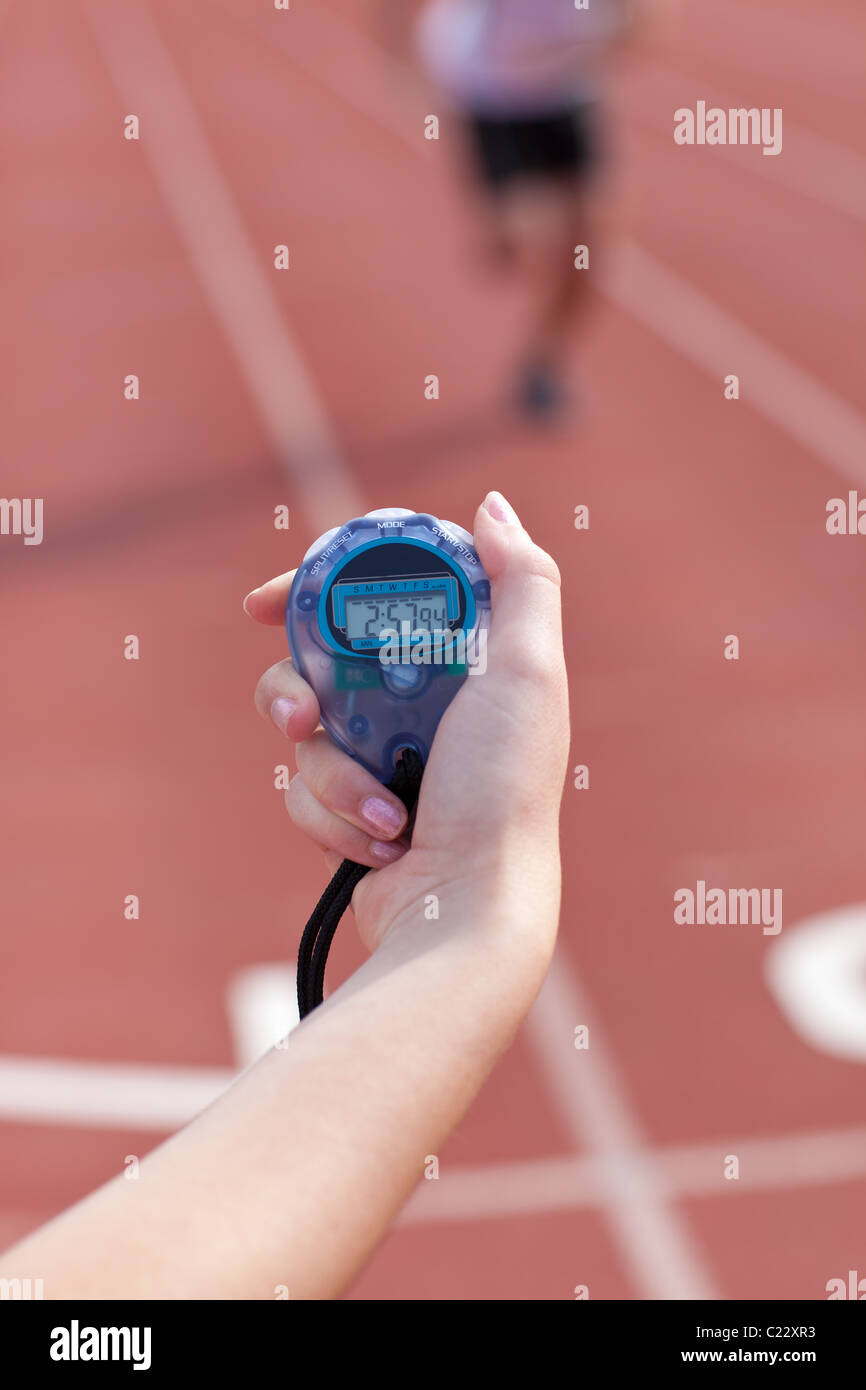 Close-up of a woman holding a chronometer to measure performances of a sprinter - Stock Image