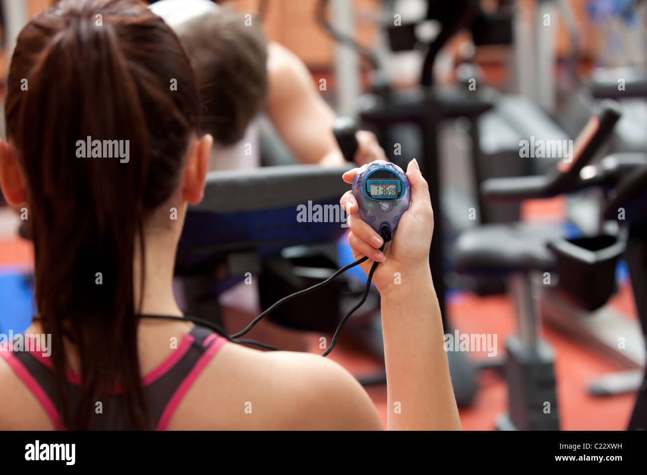 Young woman holding a chronometer and man doing physical exercise - Stock Image