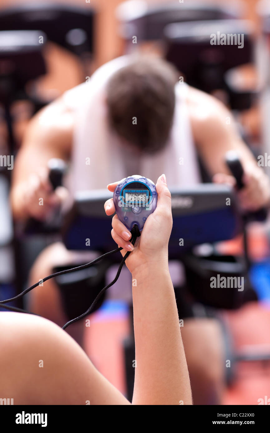 Close-up of a young woman holding a chronometer and man doing physical exercise - Stock Image