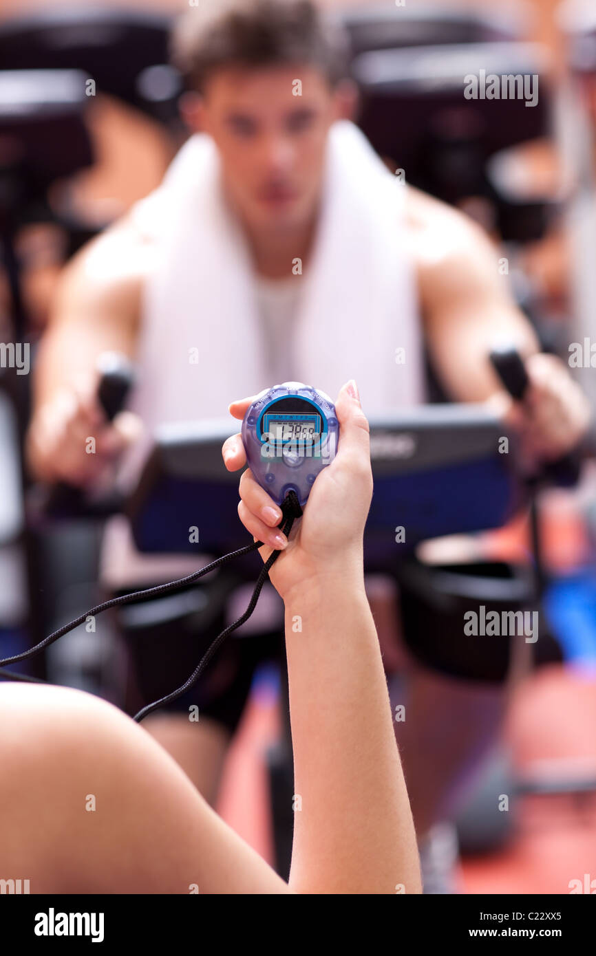 Woman holding a chronometer and man doing physical exercise - Stock Image